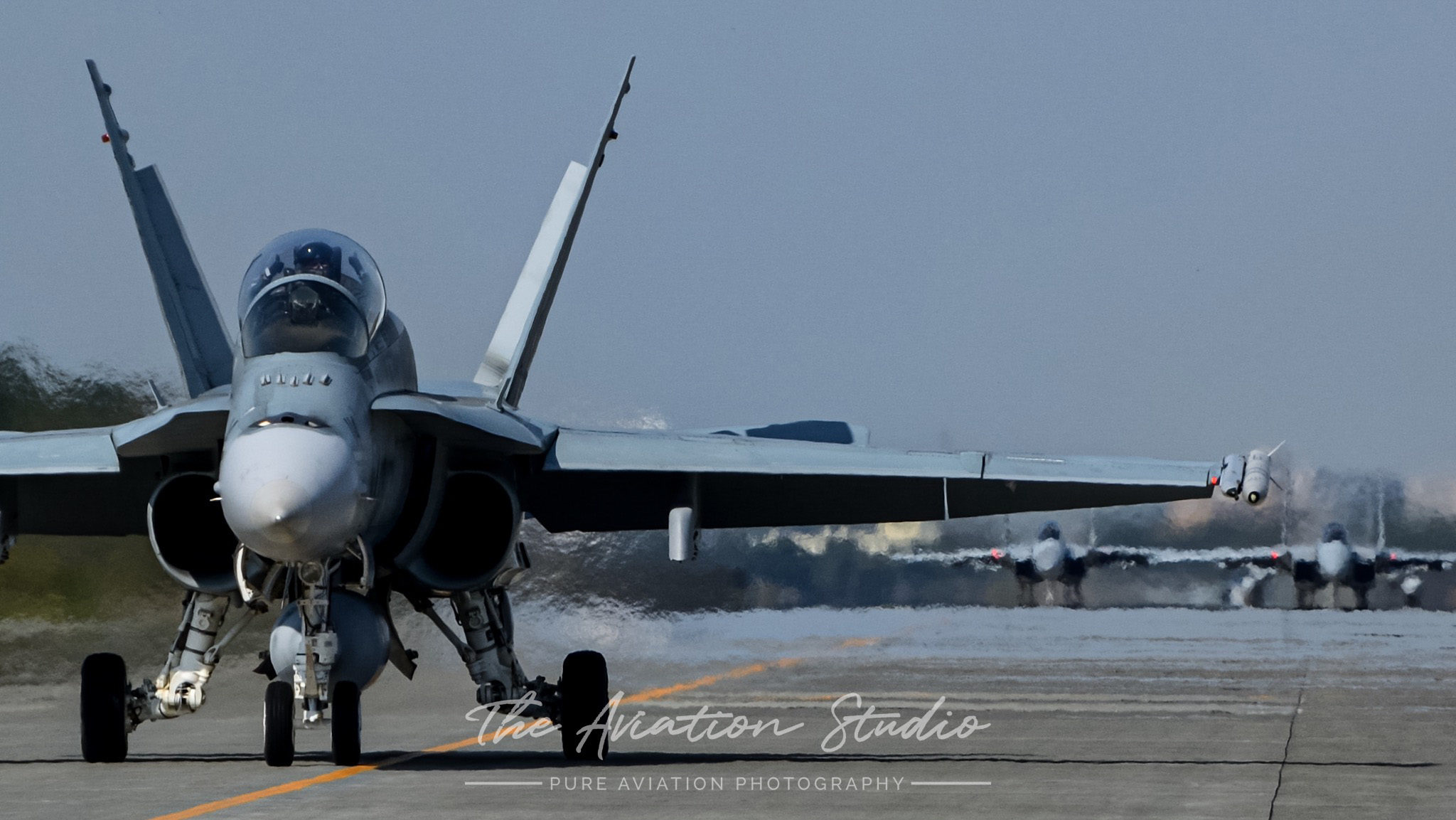 RAAF F/A-18B A21-114 taxiing at Chitose Air Base with JASDF F-15Js trailing behind