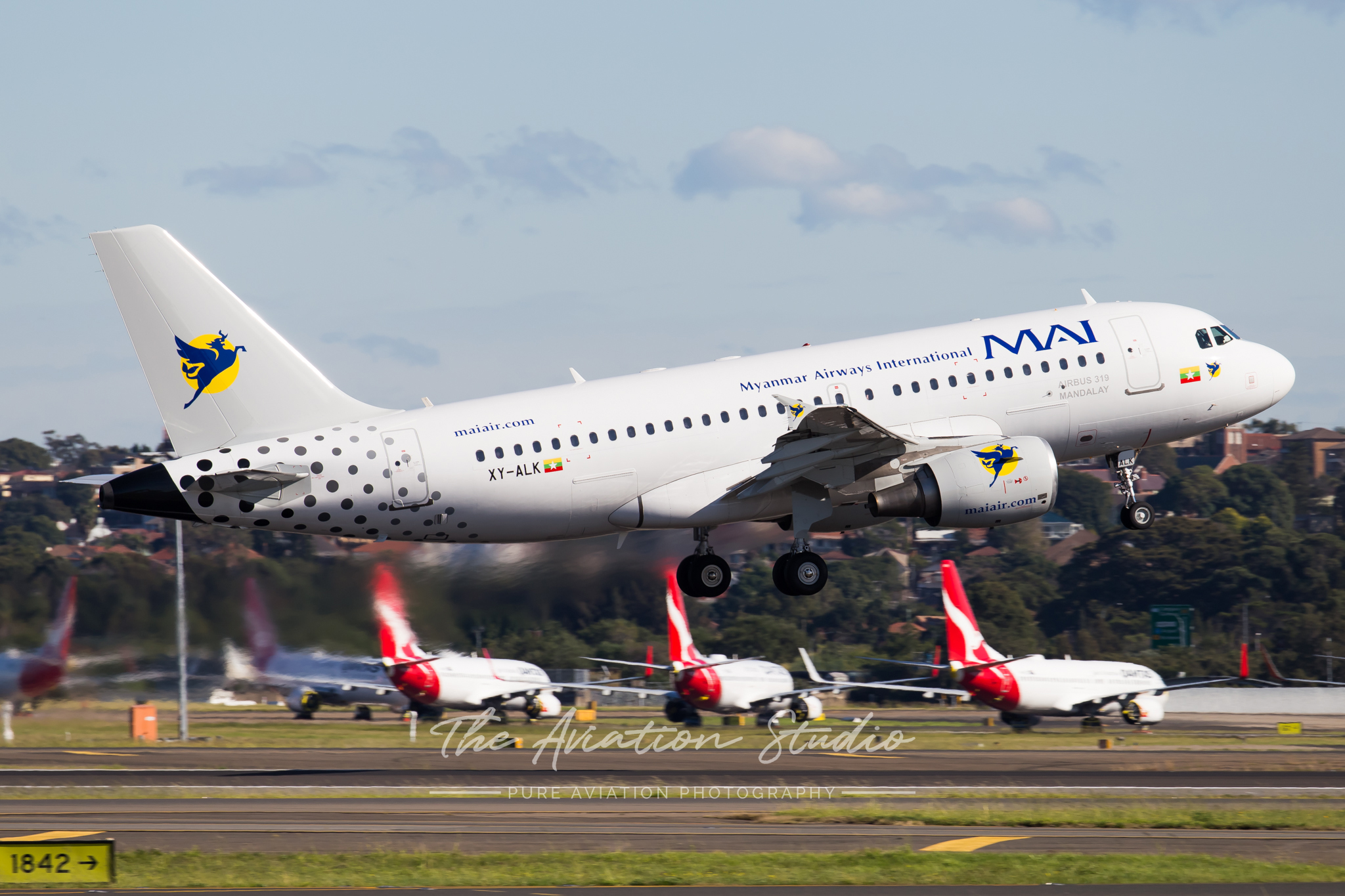 Myanmar Airways International Airbus A319-100 XY-ALK departs Sydney over stored Qantas 737s on RWY07/25 (Image: Rory Delaney)
