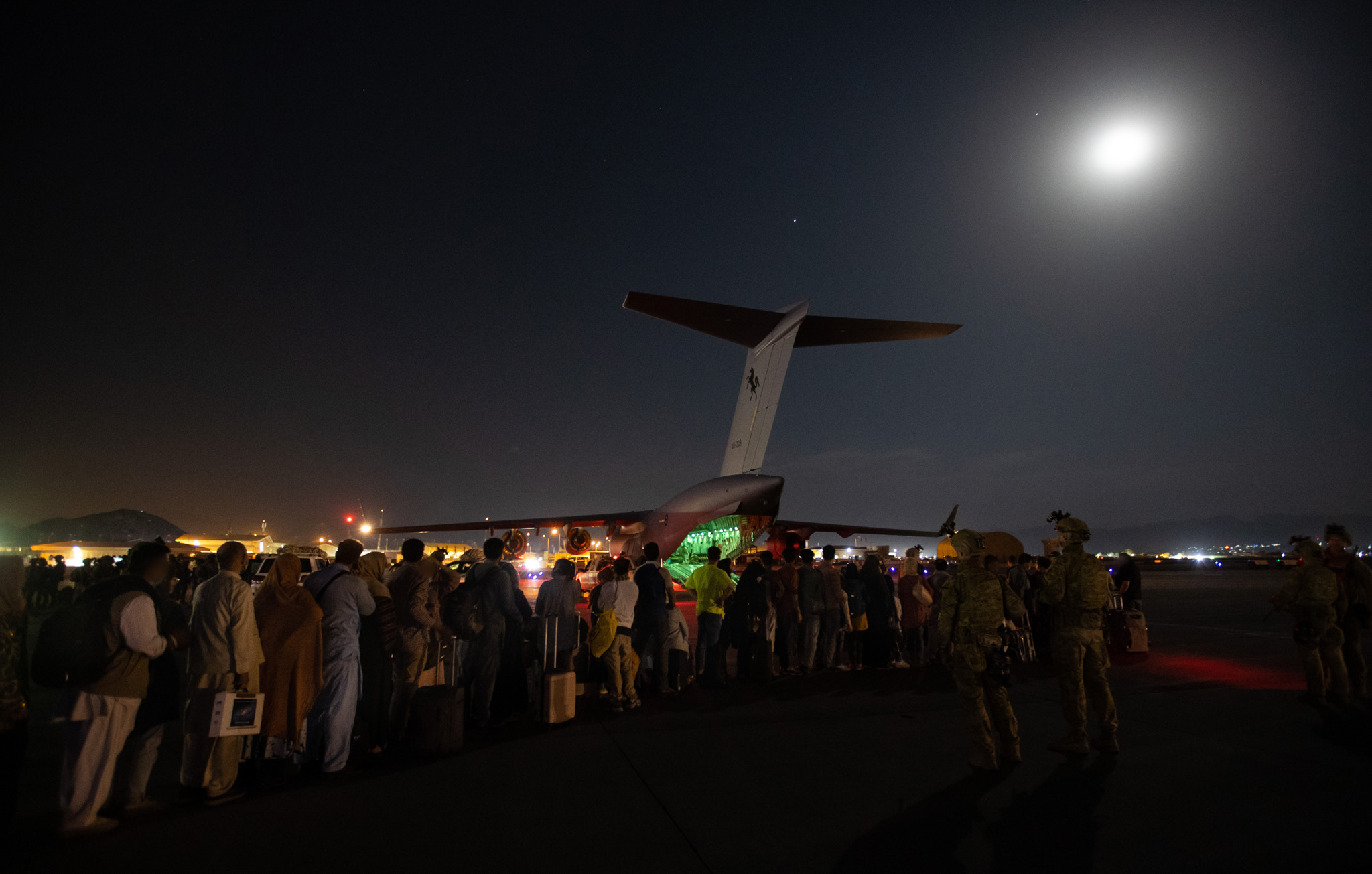 Evacuees board C-17A A41-208 as Australian Army Infantry personnel provide security in Kabul